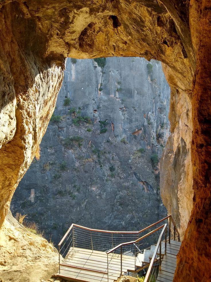 Imagen de la cueva con su enorme ventanal que muestra la pared oscura del cañón