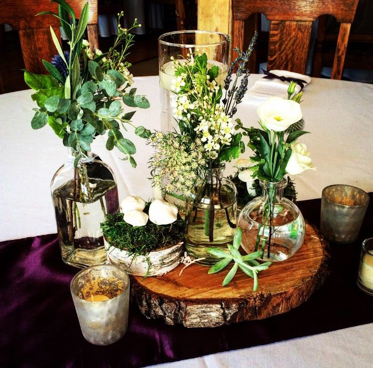 Rustic And Woodsy Wedding Centerpiece With Wood Slab Flowers In Apothecary Bottles Succulents And Cute Mushroom On Wood Bottle Centerpieces Centerpieces Wedding Centerpieces