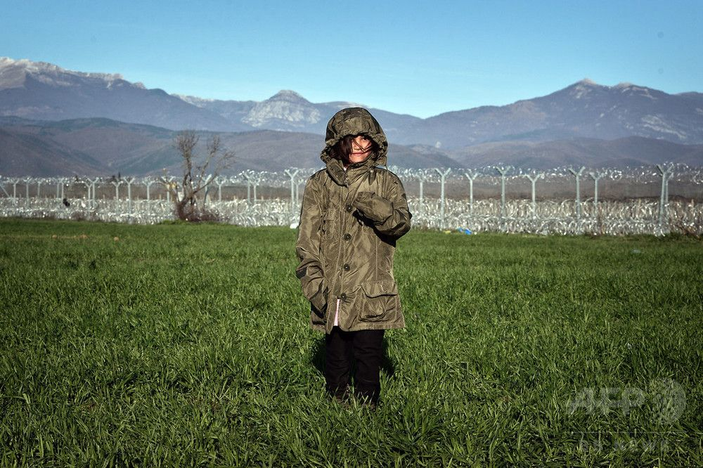 A child walks through a field by the fence of the Greek-Macedonian border near the Greek village of Idomeni, on March 5, 2016, where thousands of refugees and migrants wait to cross the border into Macedonia. (c)AFP/LOUISA GOULIAMAKI