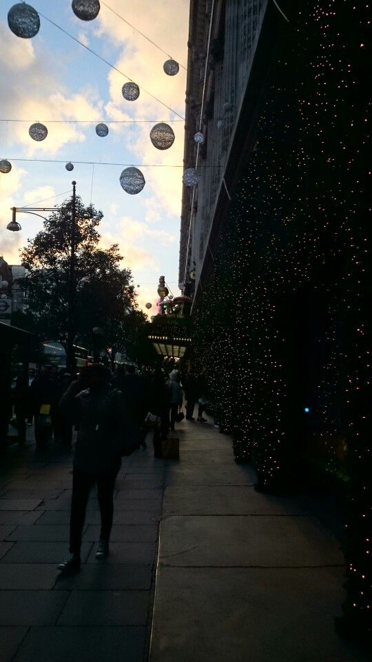 Christmas shopping on Oxford Street, London. Sun setting in the background.
