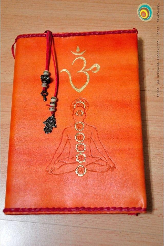 Cubierta de libro de cuero teñido, cosido de espiga, dibujo de los 7 chakras repujado y pintado en dorado, así como dibujo de ohm tibetano también pintado en dorado. Marcapáginas con tireta roja acabada en abalorios plateados.  trastocrea.wordpress.com