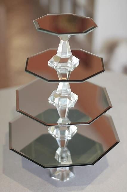 Take a visit to your discount store; Get some inexpensive crystal candle holders and mirrors. Stack and glue with E-6000 craft glue. Make for a beautiful display. Costing less is even better!