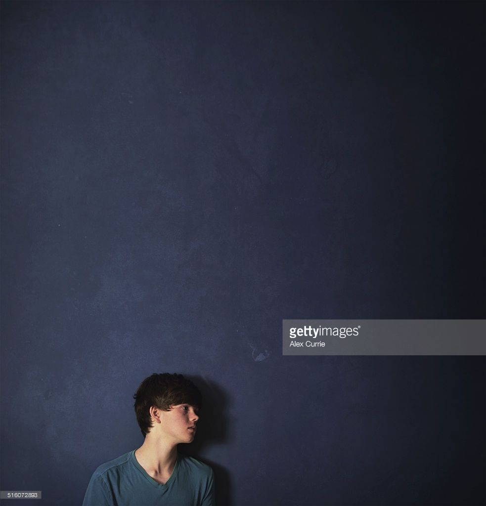 Stock Photo : Profile of teenage boy standing against blue wall staring ahead