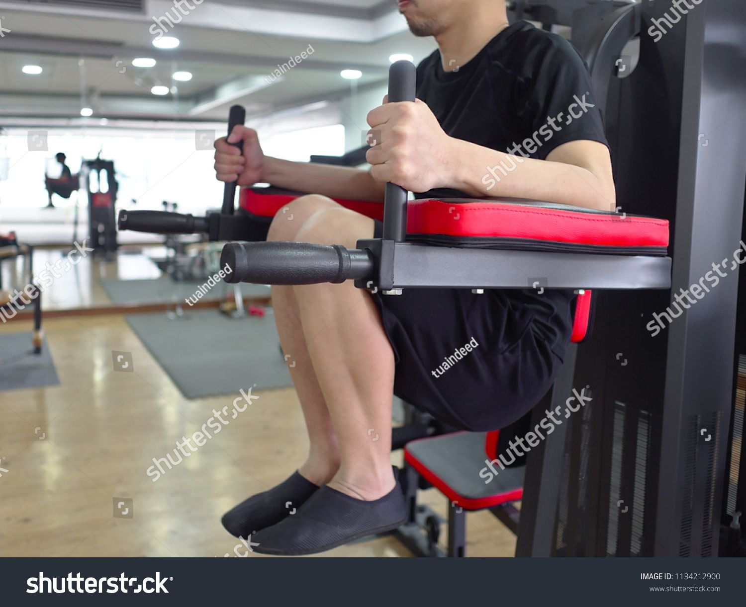 Fit young Asian man exercising with machine at sport gym. Fitness and workout concept #Ad , #Affiliate, #man#exercising#Asian#Fit