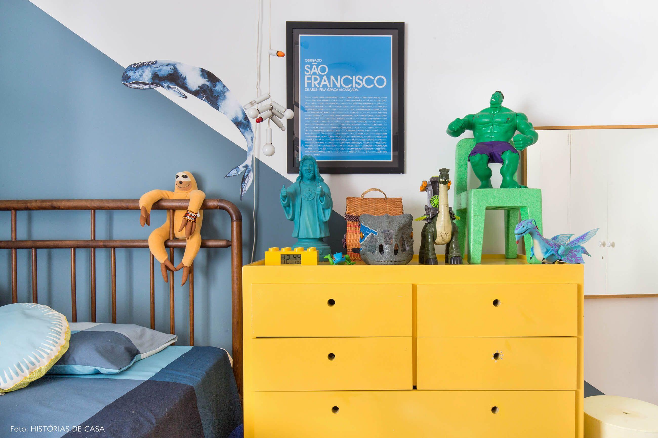 Quarto de criança com pintura em diagonal azul tem cama patente e cômoda  amarela com muitos brinquedos. ec2d415d822
