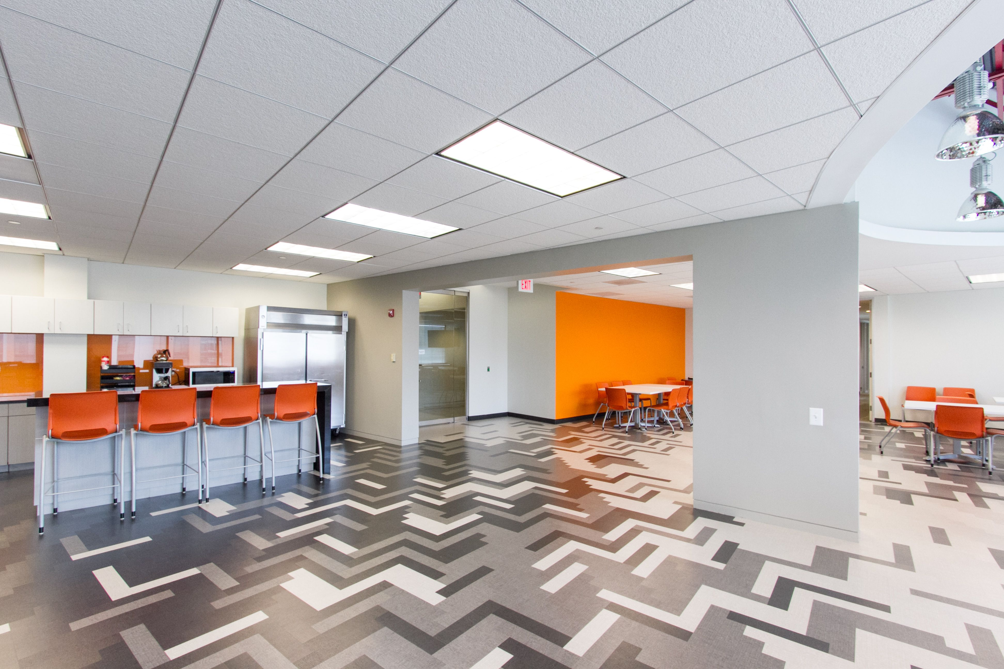 A Black, White, And Gray Break Room With Orange Accents