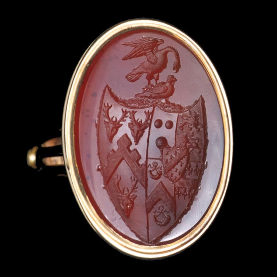 A large Georgian fob seal with a seal-engraved cornelian, theyellow gold-mounted oval cornelian seal-engraved with detailed heraldic shield and crest, the cornelian measuring approximately 3.2cms x 2.5cms, overall height approximately 4.5cms, gross weight 17.4 grams.