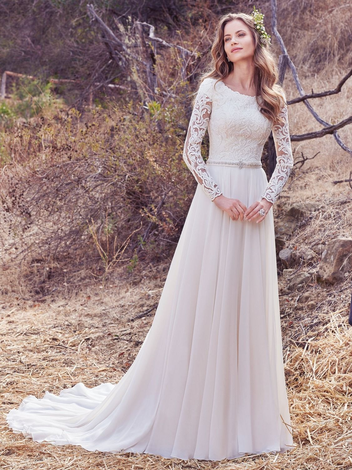 d05b2dded ... This Aurora Chiffon A-line wedding dress features a lace bodice with  illusion long-sleeves, accented in lace appliqués, over modest cap-sleeves.