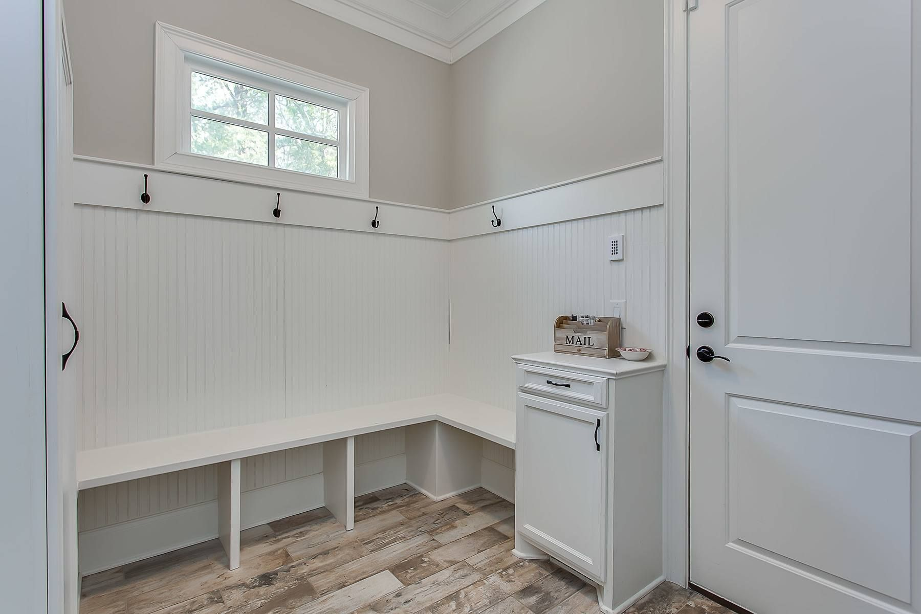 This mudroom is designed to keep an active family on the up-and-up, and the bead board and slate flooring are the understated upgrades that we love to see!