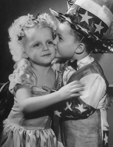 A Little Boy Dressed As Uncle Sam Kissing A Little Girl On The