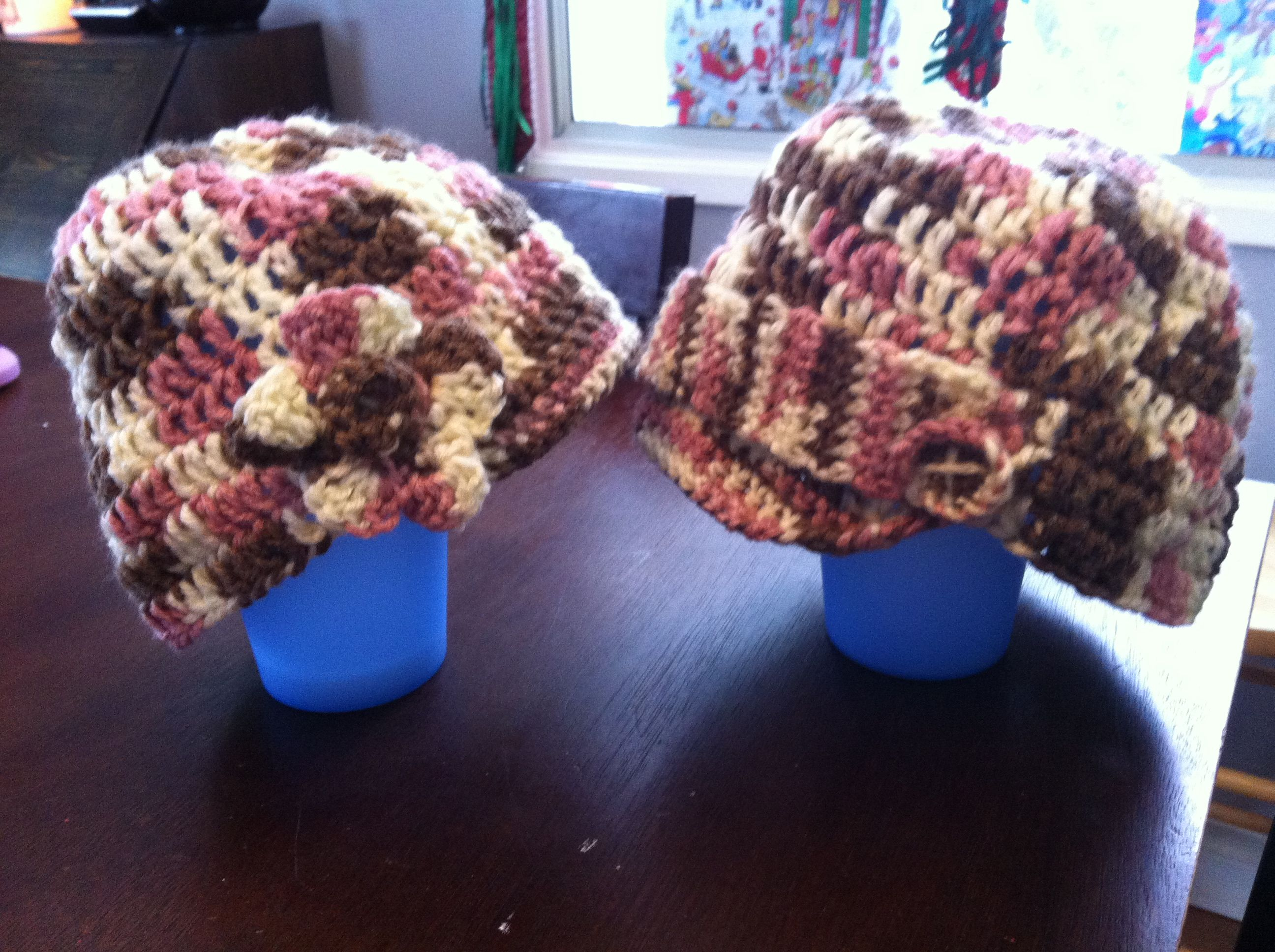 Crochet mommy and daughter hats. Mommy has a couple of buttons and daughter has a flower. Both with brims.