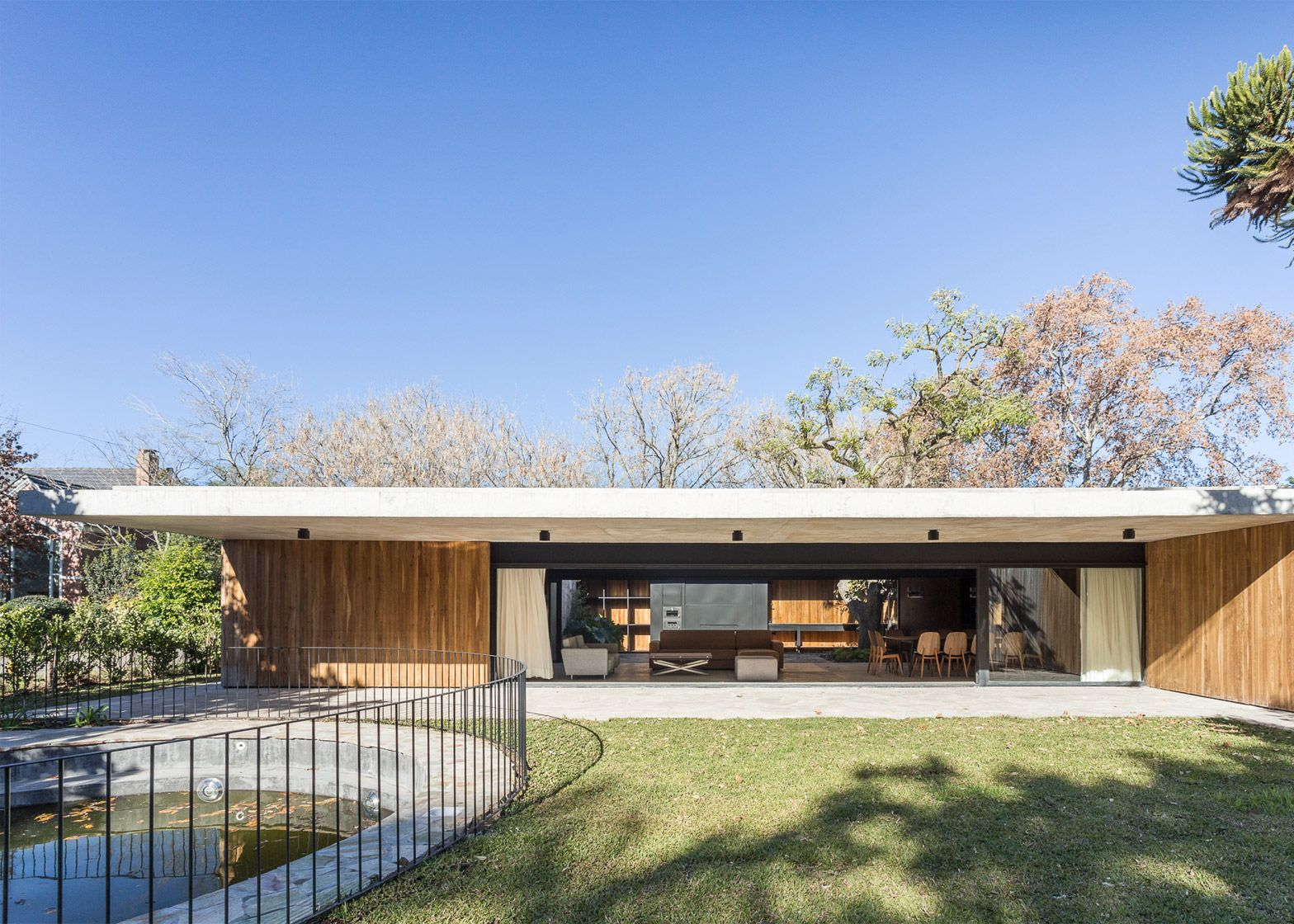 Marcelo Del Torto builds concrete home in Argentina around mature trees and plunge pool