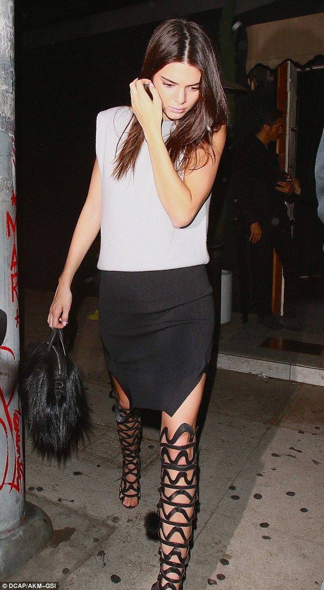 f0cfb256bd Model moment  Kendall Jenner showed off her supermodel stems to perfection  in caged thigh-high boots and a racy side-split skirt