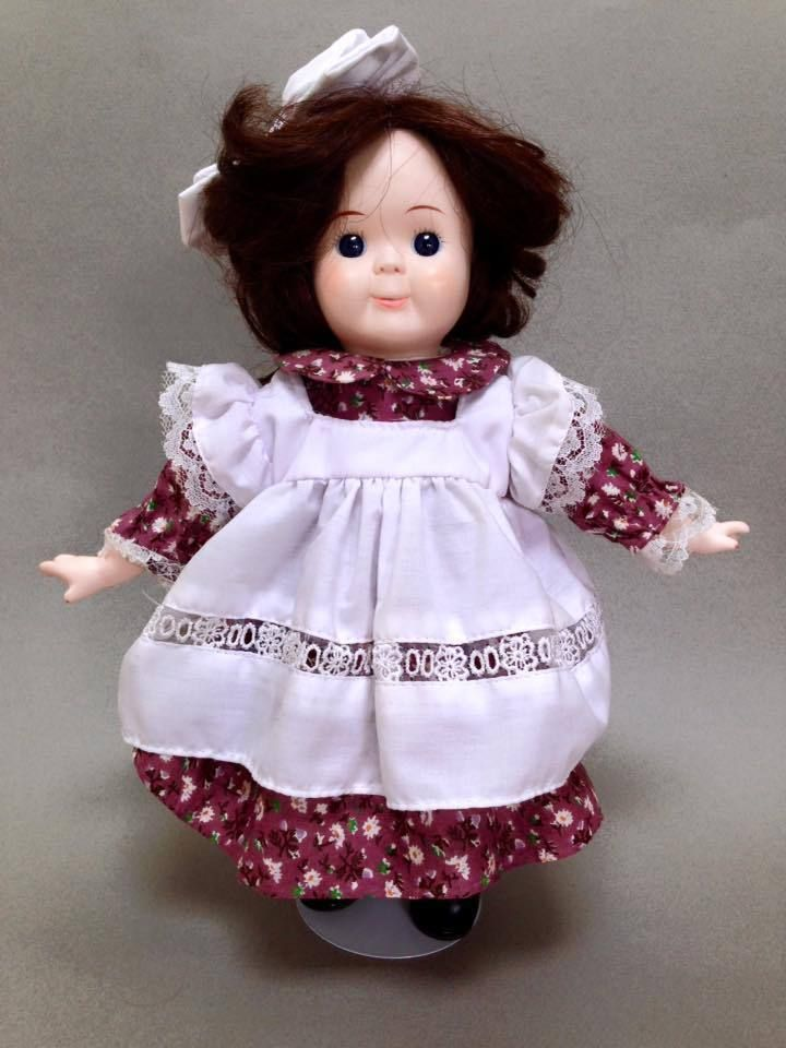 """Ok, it's another 80s doll - but wait! She's cute. Not many people in the 80s were willing to take on the challenge of creating a googly doll because it's hard to make them cute. Standing at 12"""", she wears a violet floral dress with a white pinafore. 