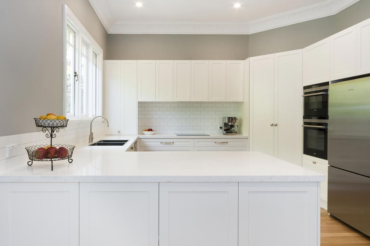 Premier Kitchens Simplistic All White Premier Kitchen Featuring Smartstone S White Kitchen Cabinet Doors White Kitchen Marble Backsplash White Modern Kitchen