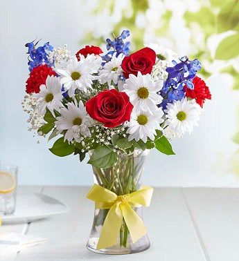 Celebrate American pride with our patriotic bouquet. Highlighted by an iconic yellow ribbon tied around the vase, this hand-designed arrangement of red, white and blue blooms is a beautiful way to celebrate a national holiday or to honor a hero in your life. All-around arrangement with red roses, white daisy poms and blue delphinium; accented with baby's breath and assorted greenery Artistically designed in a clear glass vase accented with a yellow satin ribbon; measures 8