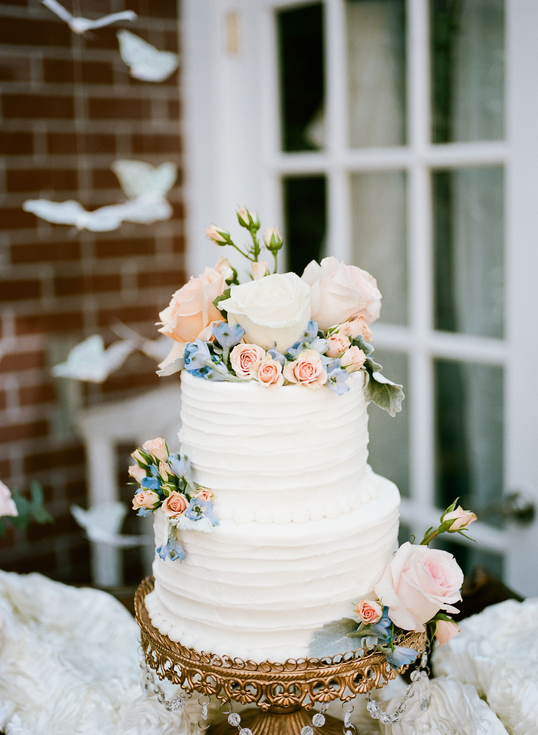 Buttercream wedding cake with blush and blue flowers outdoor buttercream wedding cake with blush and blue flowers izmirmasajfo Images
