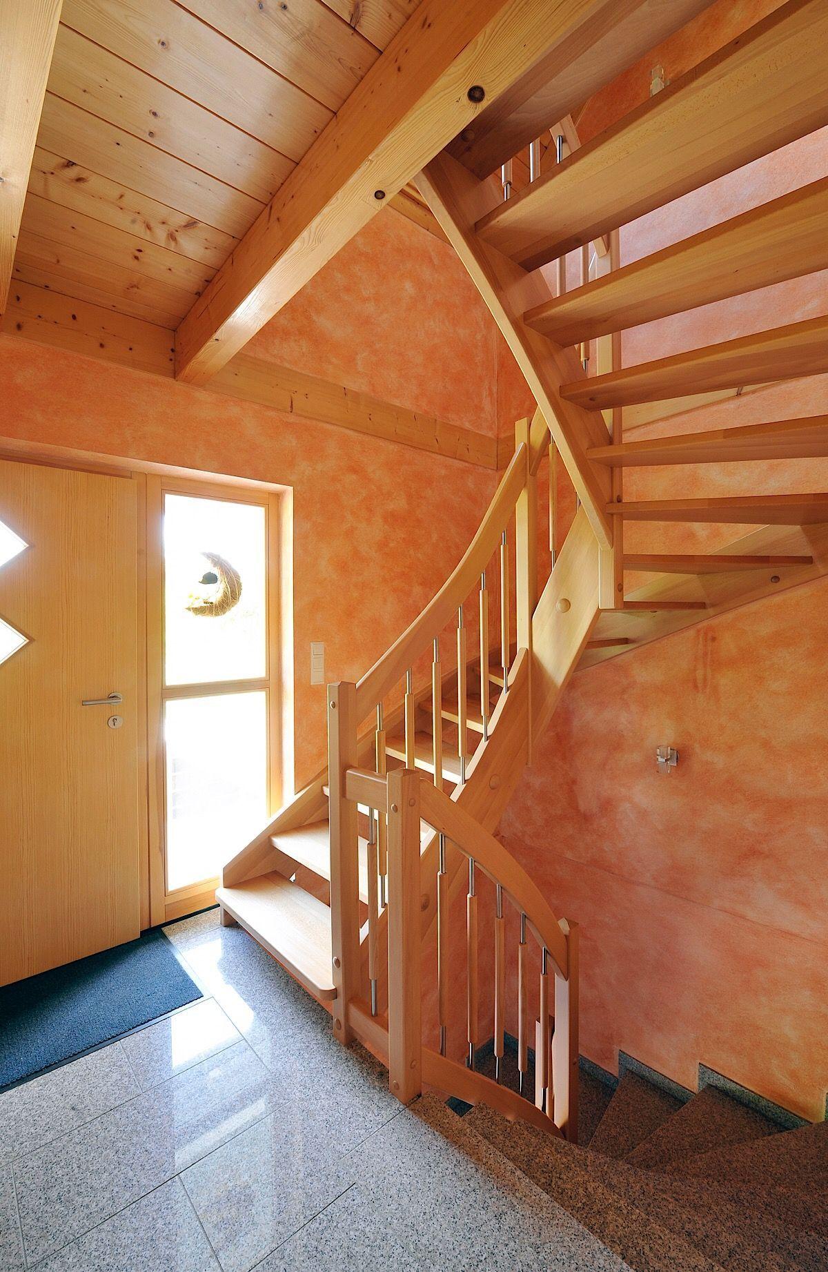 Holzhaus innen mit offener Holztreppe im Eingangsbereich