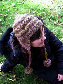 One of my first designs, Lichen is a classic earflap hat that has been keeping me warm for years! Moss stitch stripes add texture to this easy knit. The earflaps are knit flat first, then joined in the round at the brim and worked to the crown at the top of the head. A fluffy pom-pom can be applied to the crown or, as shown, suspended from the earflaps. Instructions are given for two sizes suitable for the average woman or man's head.