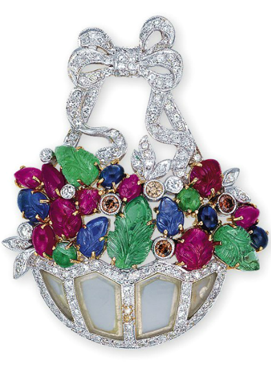 A MULTI-GEM PENDANT/BROOCH  The rock crystal basket lined with single-cut diamonds, filled with cabochon sapphires and emeralds, carved emerald leaves, carved ruby and sapphire floral buds, accented by brilliant-cut brown diamonds, mounted in 18k white and yellow gold, 4.9 cm long
