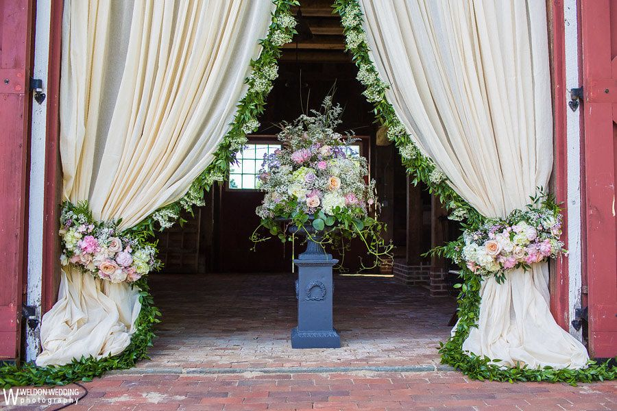 A gorgeous floral curtain to frame this barn ceremony