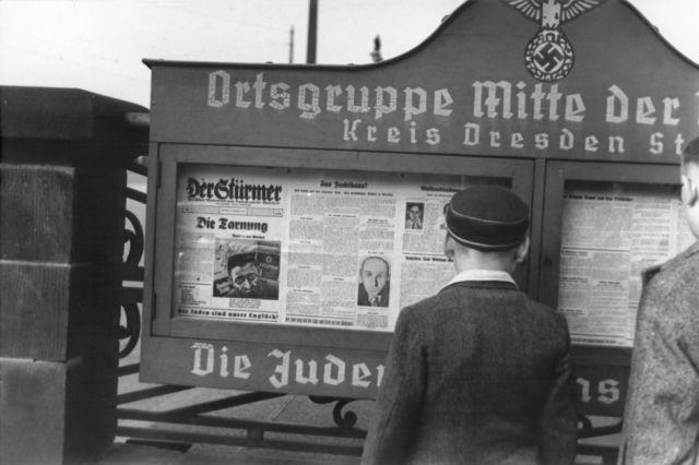 """Meninos alemães lêem edição do jornal """"Der Stuermer"""" afixado a um mural na entrada da sede do Partido Nazista na região de Dresden. O slogan alemão (parcialmente escondido), na parte inferior do mural diz, """"Os judeus são a nossa desgraça."""""""