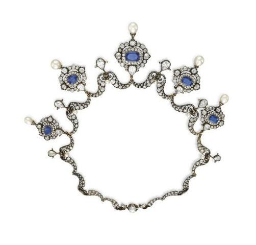 A diamond, sapphire and pearl tiara necklace, shown here off its frame. Designed as a series of five sapphire motifs, surrounded by diamonds and topped with a pear-shaped pearl, with smaller spacers, topped pear-shaped diamonds. Sold by Christie's at some point in 2007.