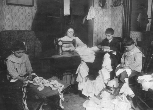 Mother and three sons work on dresses for for Campbell Soup Kid dolls - New York, 1912