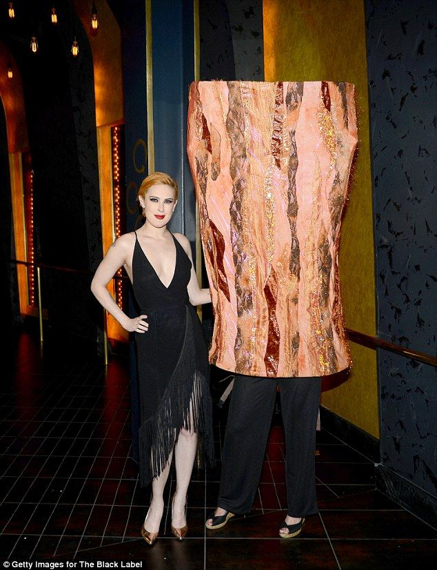 Sizzling: The star looked typically glamorous with a vivid red lipstick and a thick kohl-lined eye, her skin once again the perfect shade of porcelain as she posed against a strip of bacon