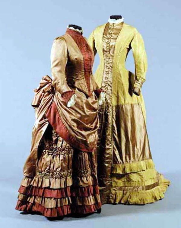 Left: cinnamon satin & velvet walking outfit, ca. 1875-78, comprising fitted bodice and skirt with smocked and pleated satin detailing. Right: mustard-colored satin day dress with pale brown satin contrasts, ca. 1876; princess cut. Sotheby's