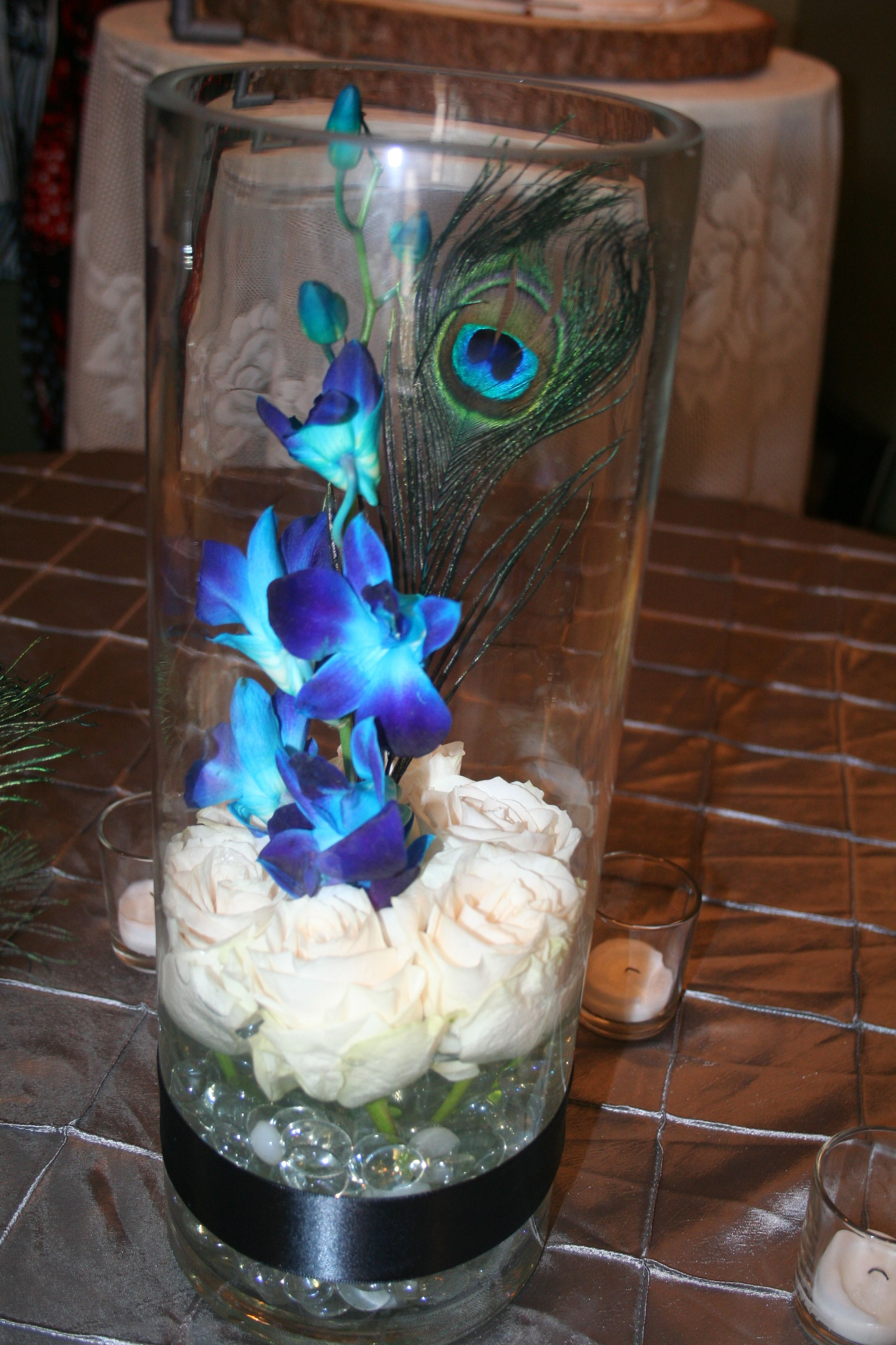 "Inexpensive centerpiece of a 15"" tall cylinder vase with white roses"