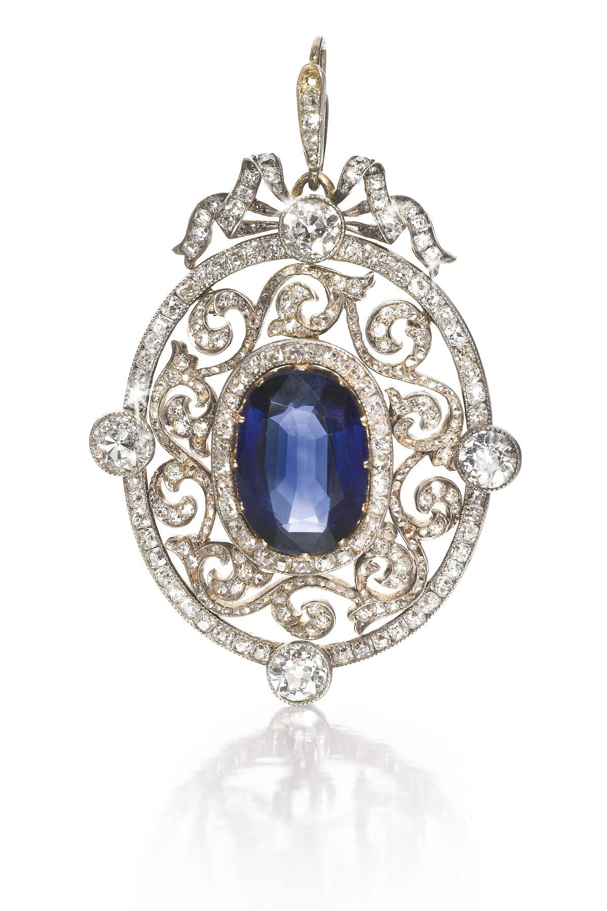 A Fabergé jewelled gold pendant, Moscow, 1899-1908. the oval sapphire claw-set within an openwork rose-cut diamond-set scroll frame and four large circular-cut diamonds, ribbon surmount, struck KF in Cyrillic, 56 standard, scratched inventory number 316?38 height including suspension loop 5cm, 2in.