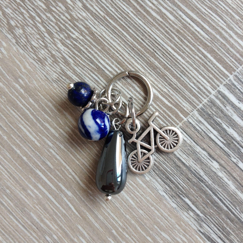 Bedel van metalen fiets, hematiet druppel, 8mm keramiek met Delfts blauw beschildering en 6mm lapis lazuli met metalen sierkap. Van JuudsBoetiek, €5,50. Te bestellen op www.juudsboetiek.nl.