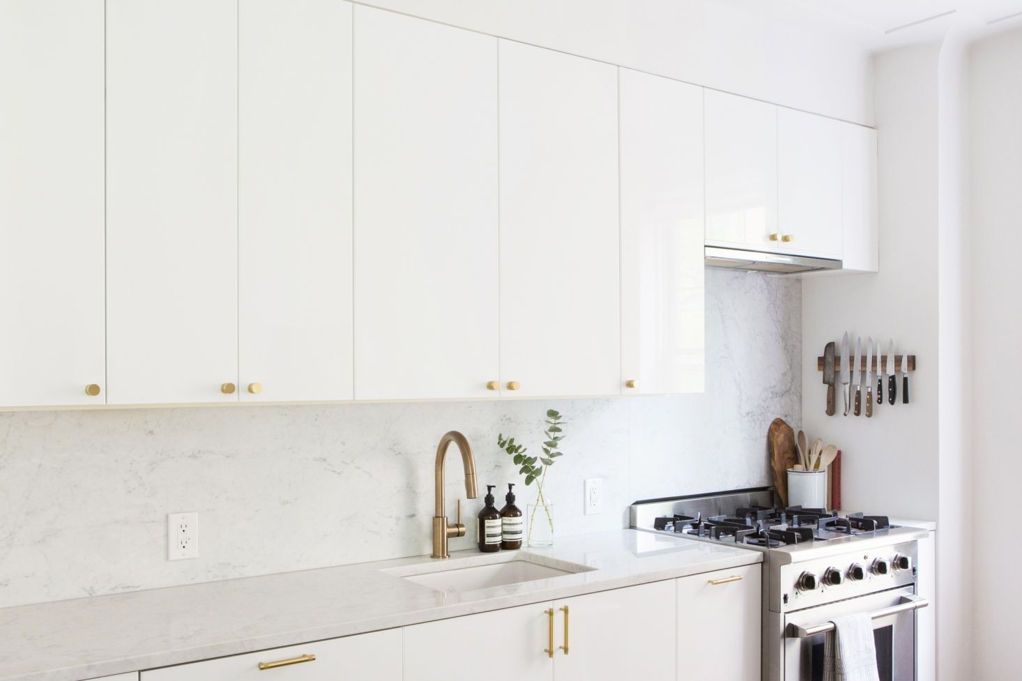 Kitchen Of The Week An Ikea Kitchen With An Elegant Upper Cabinet Solution Remodelista White Ikea Kitchen White Glossy Kitchen Ikea Kitchen