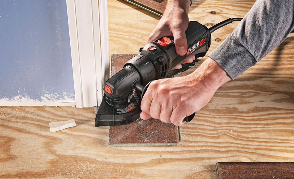 A Man Uses A Saw To Prepare Door Jambs For New Flooring Installing Laminate Flooring Laminate Flooring Diy Laminate Flooring
