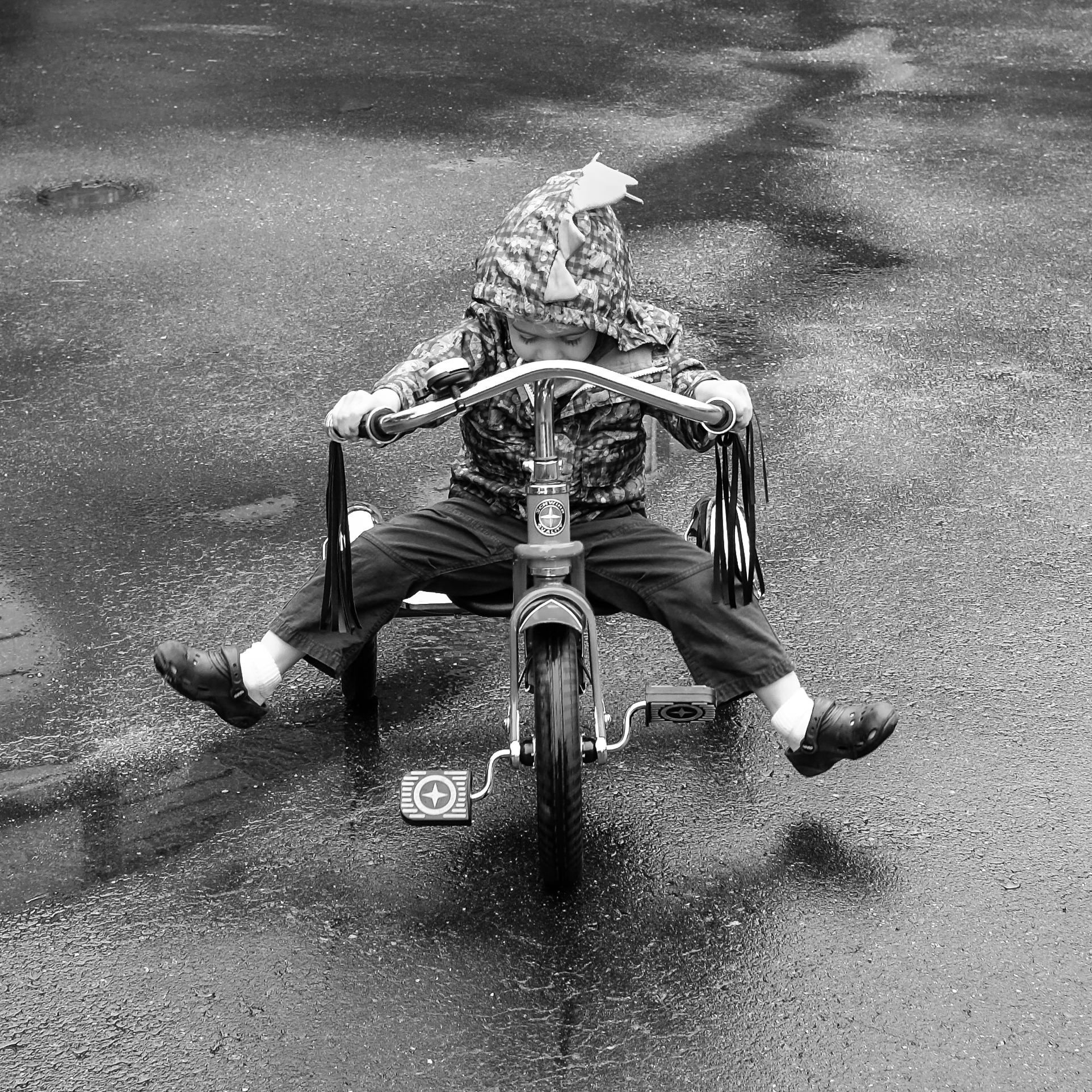 A young boy enjoys his tricycle in the rain.