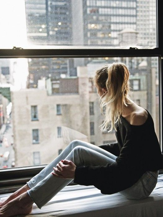 Chica sentada en la ventana viendo hacia la ciudad