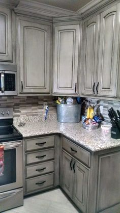 These gray kitchen cabinets that feature slab door styling ...