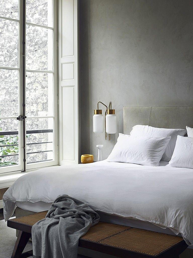 joseph dirand bedroom with white linens, caned bench, and gold sconce - The  gold sconces really drew my eye into this room decor.