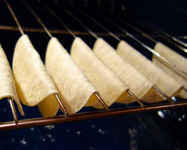 Warm tortillas so they are pliable. Then spray or brush with oil. Place over oven rack bars. Bake at 375 for 7-10 minutes.