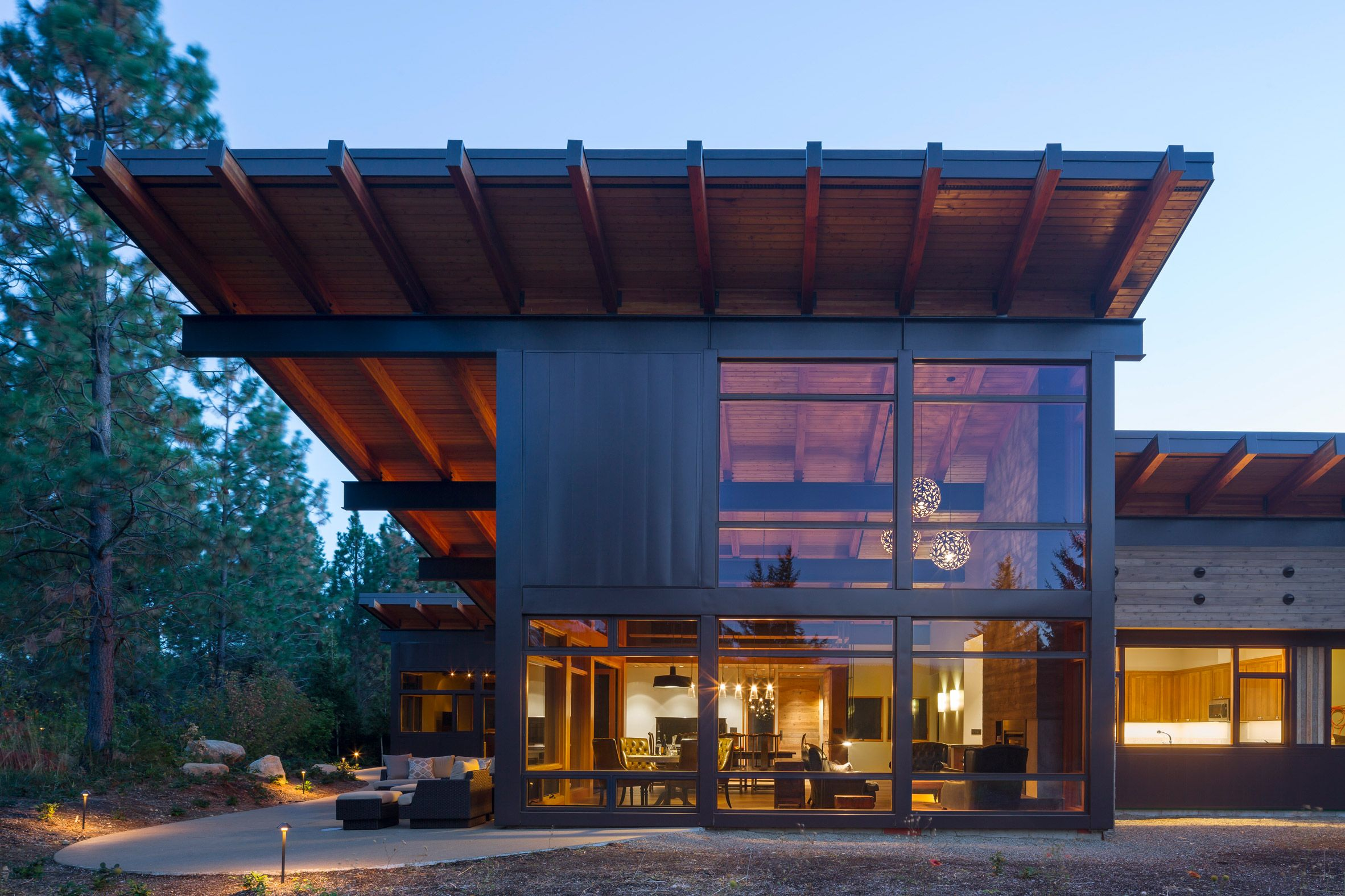 Steel beams support dramatic roof overhangs at washington state retreat by coates design