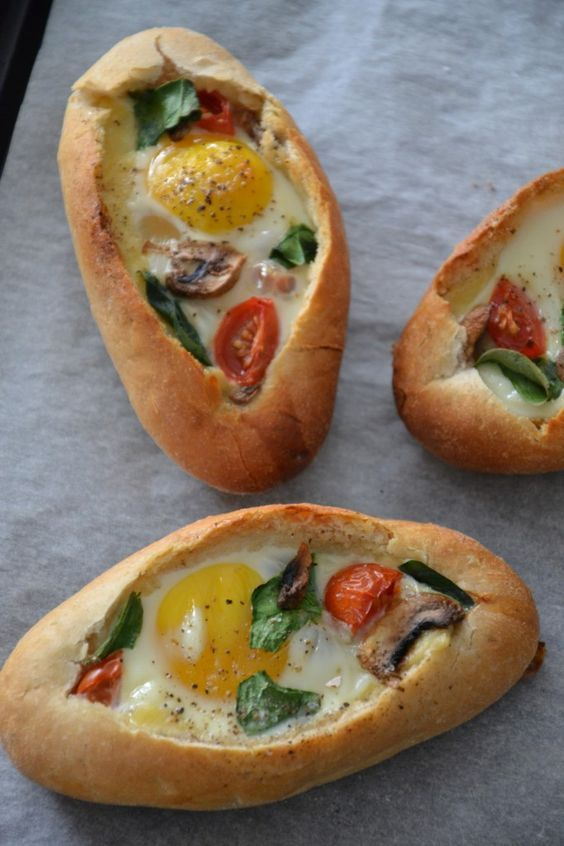 Breakfast Egg Boats ~ small buns or baguettes sliced and filled with cherry tomato, spinach, mushrooms, and cheese, then topped with an egg and baked in the oven ~ nutritious & easy brunch option | recipe from BrendaKookt.nl via Google Translate