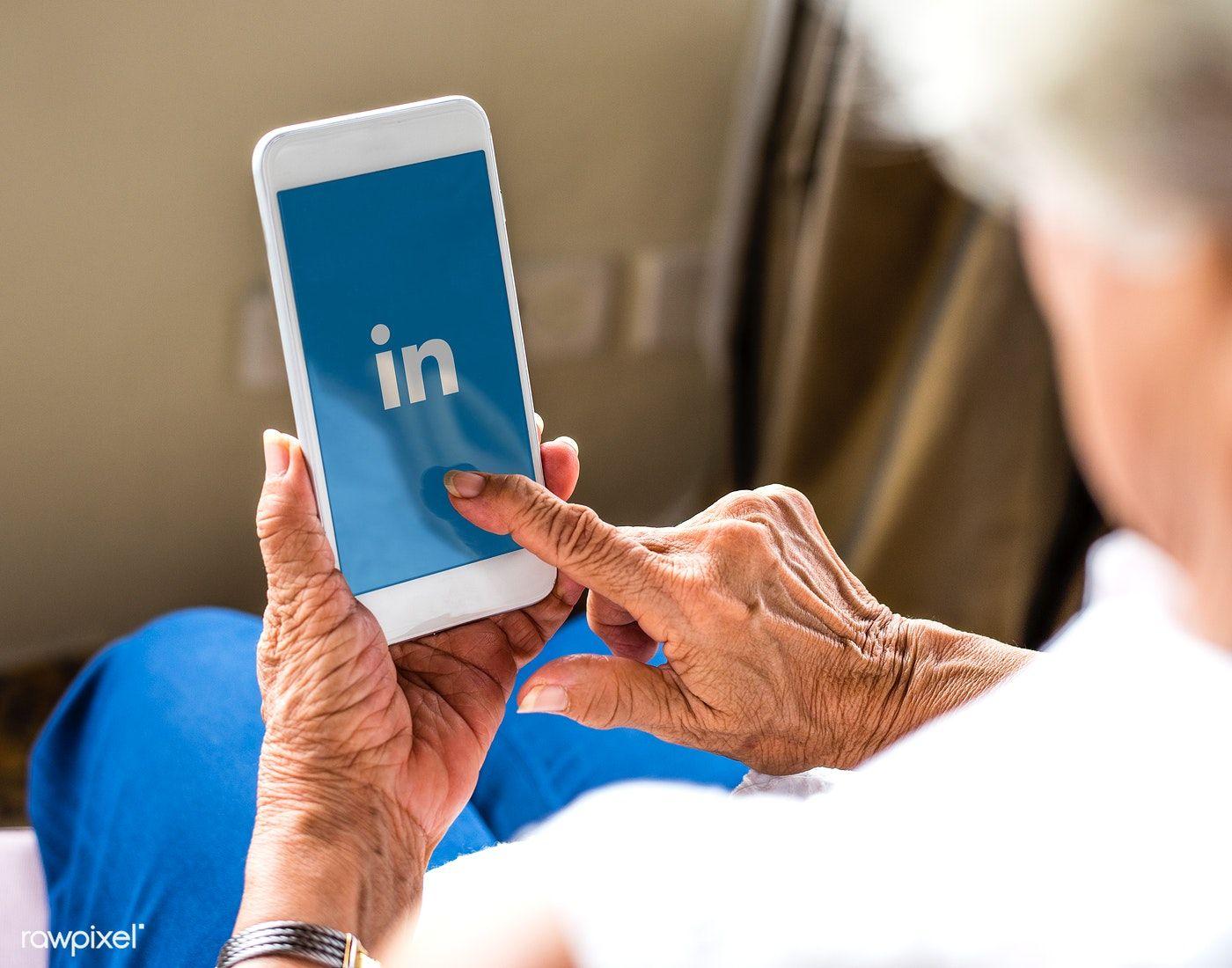 Elderly woman using linkedin application on a mobile phone