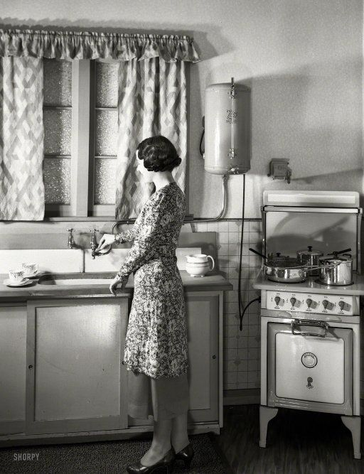 "new zealand circa 1930s. ""model at sink in kitchen equipped with"