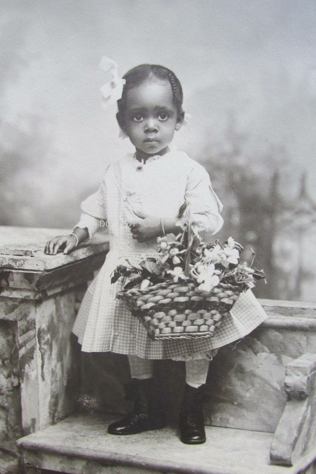 A beautiful little girl holding flowers in a basket 1890s