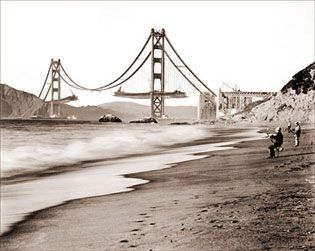 The Golden Gate Bridge under construction. Designed by Joseph Baerman Strauss and built during the Great Depression, it remains one of the world's great engineering feats.  The roadway was extended from the towers symmetrically to keep the structure balanced. Work on the Golden Gate Bridge began on 1/5/33 was opened to pedestrians on 5/27/37 and, after the opening ceremonies, to vehicular traffic the following day.  This photo shows fishermen on Baker Beach in San Francisco.