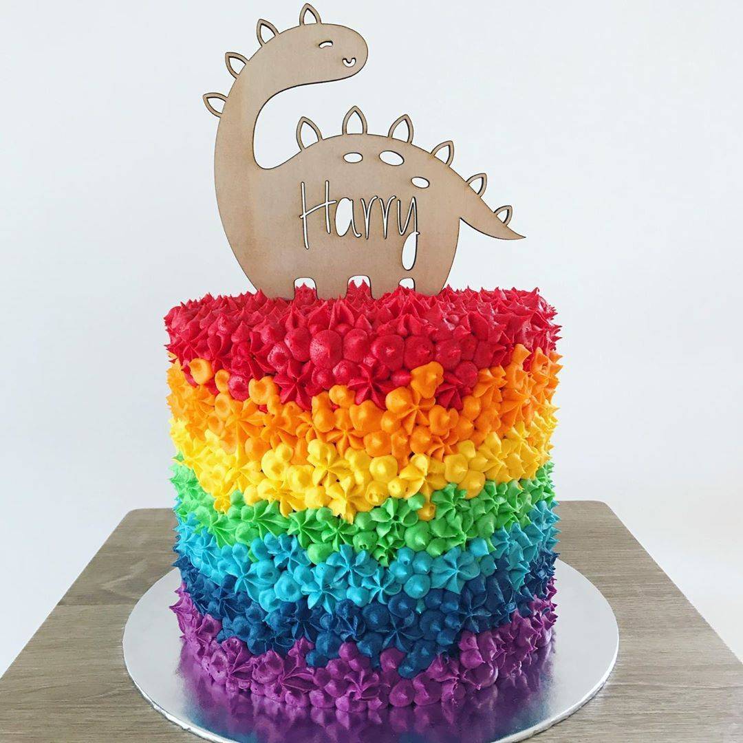 Piping rainbows all day 🌈Layers of rich chocolate cake and chocolate buttercream, covered in full technicolour. Cute happy dino cake topper by @anroldesigns 🦕 ...