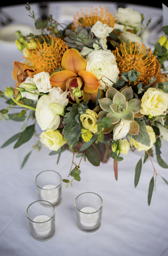 Tropical Dining Table Centerpiece With Orange Cymbidium Orchids Pin Cushion Protea White R Yellow Centerpieces Tropical Dining Tables Ranunculus Centerpiece