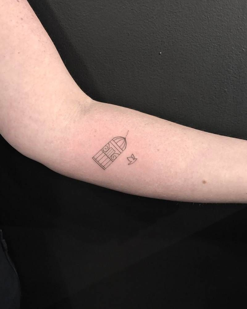 Fine Line Bird Coming Out Of A Bird Cage Tattoo On The Inner Forearm Cage Tattoos Birdcage Tattoo Small Bird Cage
