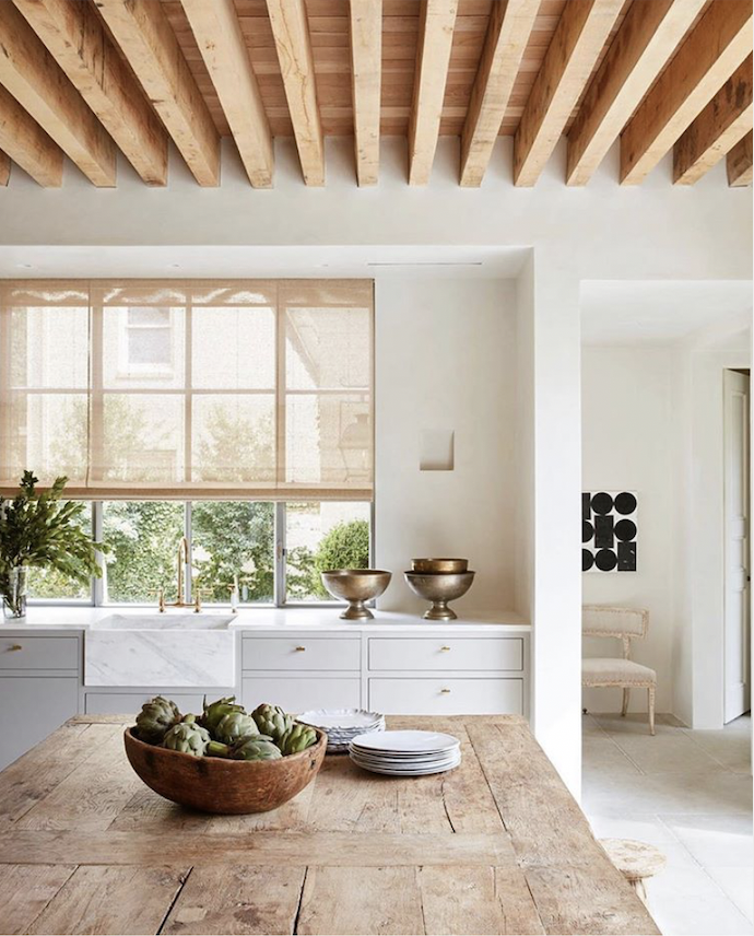 This kitchen is everything we stand for natural, with a touch of glam. We love how the wood ceiling and raw rustic table juxtapose the clean cabinets, gold pulls, and marble sink! Absolutely beautiful ❤️ design by @jilleganinteriors #kitchen #kitchentrends #kitchen2019 #woodceilings #interiors2019 #beautifulkitchen #interiordesignkitchen